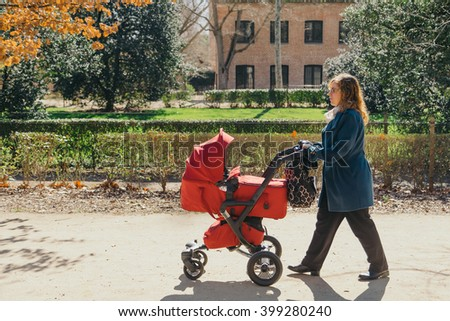 Mother walking with baby stroller in park
