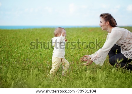 Mother walking with her baby in spring green field - stock photo