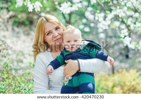 mother walking with her baby son in garden of blooming magnolias