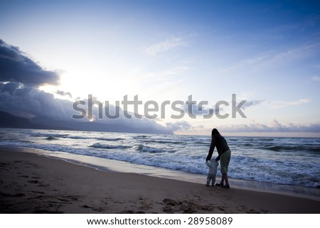 mother walking with her little son along the beach - stock photo