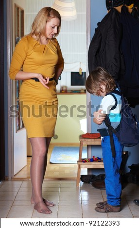 Mother warns her son in hallway after coming back from school - stock photo