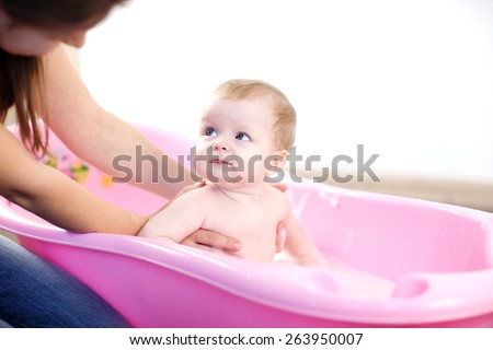 Mother washing a baby in pink bathtub