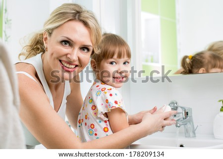 mother washing baby hands - stock photo