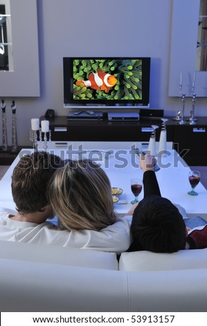 Mother watching TV with her children. - stock photo