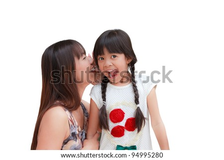 Mother whispering secrets in her daughter's ear - stock photo