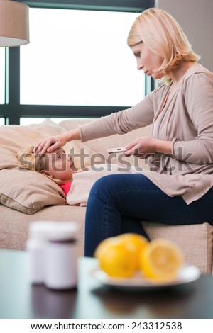 Mother will take care of you. Mother holding thermometer and touching forehead of her ill daughter lying on the couch  - stock photo