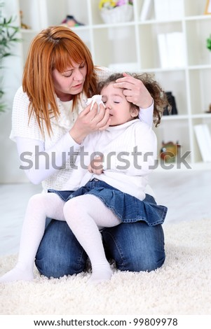 Mother wiping sick daughters nose with tissue - stock photo