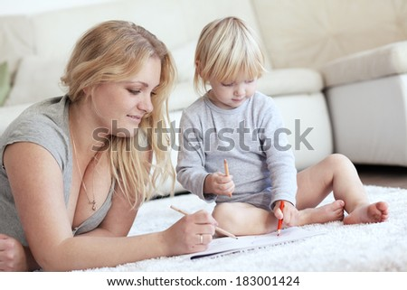 Mother with a child drawing together at home - stock photo
