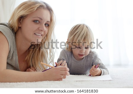 Mother with a child drawing together on a carpet at home