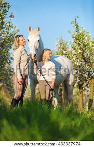 Mother with a daughter and a white horse in blooming garden - stock photo