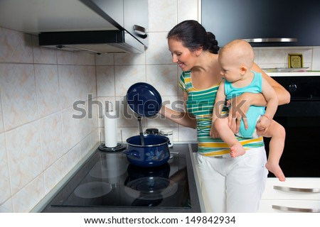 mother with a newborn baby cook food in the kitchen