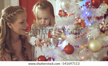 Mother with adorable baby decorate a Christmas tree at home