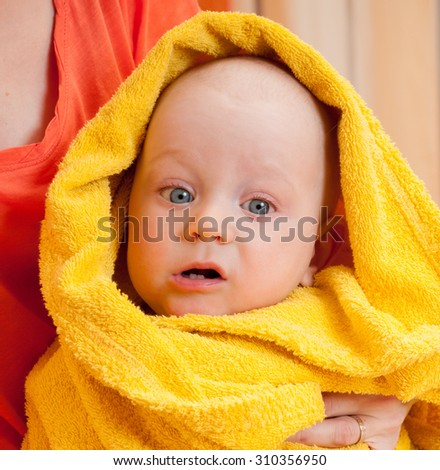 Mother with adorable pretty baby, kid covered with bath towel. After shower. Happy family portrait.
