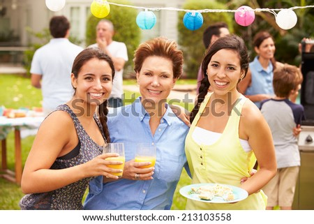 Mother With Adult Daughters Enjoying Party In Garden - stock photo