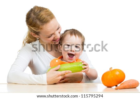 Mother with baby at table. Boy holding zucchini - stock photo