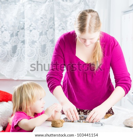 Mother with baby baking gingerbread cookies in kitchen