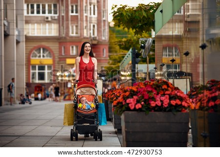 Mother with baby carriage on city street summer