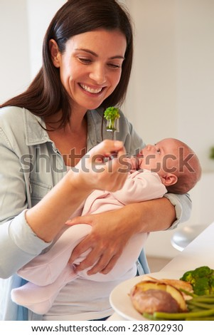 Mother With Baby Eating Healthy Meal In Kitchen - stock photo