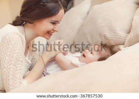 mother with baby girl. Portrait of happy young attractive mother lying with her baby on the bed at home. Mother playing with cute baby girl indoor. Portrait of angelic baby and mother - stock photo