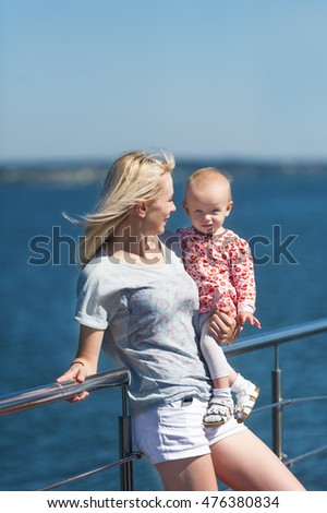 Mother with baby girl stand on jetty by the river. Tender feelings of mother to the baby.