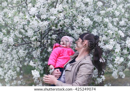 mother with baby in apple garden - stock photo
