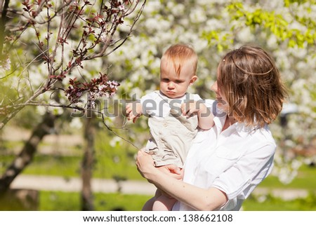 Mother with baby  in garden - stock photo