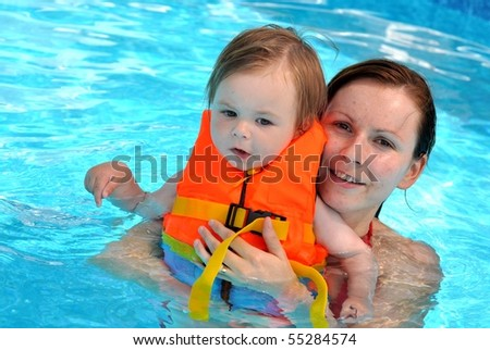 mother with baby in pool - stock photo