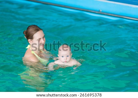Mother with baby in swimming pool training - stock photo