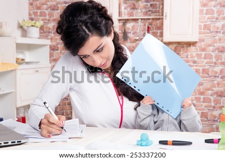 Mother with baby in the kitchen working with documents - stock photo