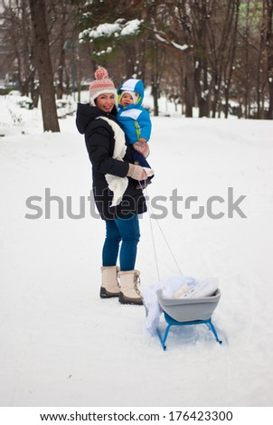 Mother with baby in winter park holding sleigh - stock photo