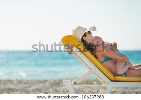Mother with baby laying on sunbed on beach - stock photo
