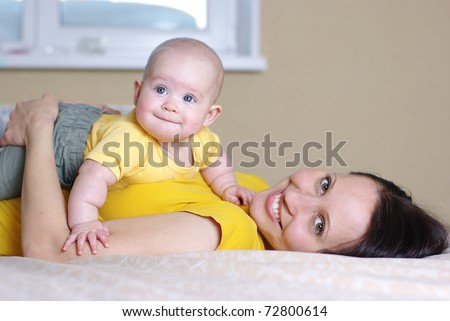 Mother with baby on bed - stock photo