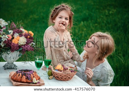 Mother with baby on picnic. Little girl eats chocolate cake. The concept of life values, peace, security and love
