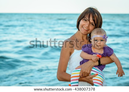 Mother with baby on sea background. mother is not in focus. Mother and daughter on vacation. Mother's Day, Thanksgiving Day, happy childhood, concept of family life, summer holiday with baby