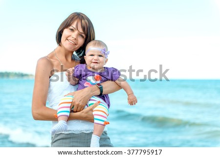 Mother with baby on sea background. my mother is not in focus. Mother and daughter on vacation