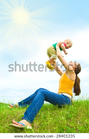 Mother with  baby  on the meadow under blue sky - stock photo