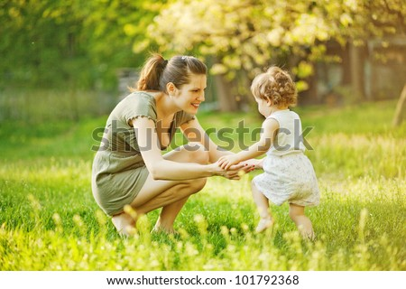 mother with baby outdoors - stock photo
