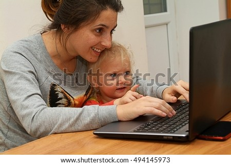 Mother with baby playing on laptop