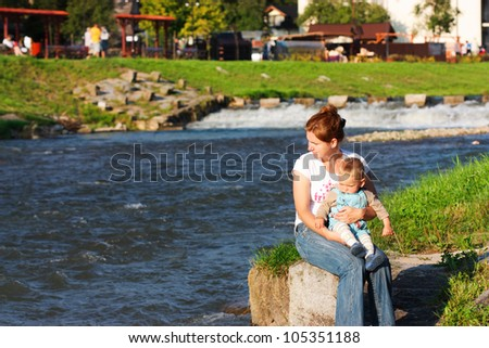 Mother with baby resting on riverside - stock photo