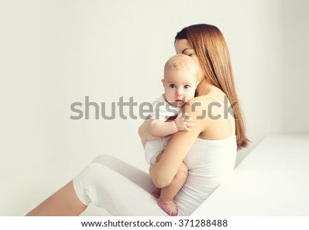 Mother with baby sitting home in white room near window