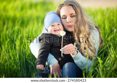 Mother with baby son on the meadow playing with dandelion flower