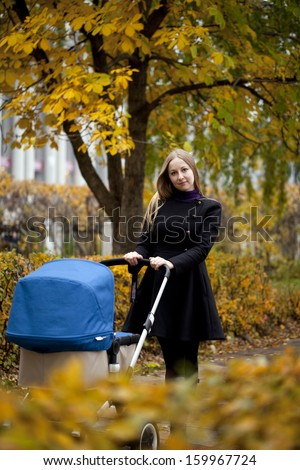 Mother with baby stroller for a newborn in autumn park