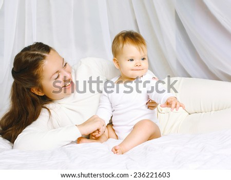 Mother with baby together on the bed