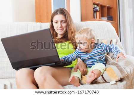 mother with baby working online with laptop at home