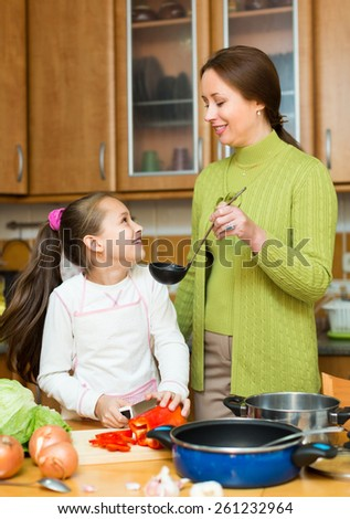 Mother with cheerful preschooler daughter cooking at home kitchen together and smiling. Focus on girl