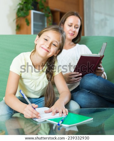 Mother with cheerful schoolgirl doing homework in the living room at home. Focus on girl - stock photo