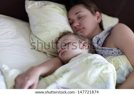 Mother with child are sleeping on a bed in the morning - stock photo