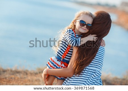 mother with child girl by the sea. Sunset portrait. Outdoor. Summer. Woman with girl. Happy family relaxing by sea. Relaxed young mother standing on the shore with her playful little daughter.  - stock photo
