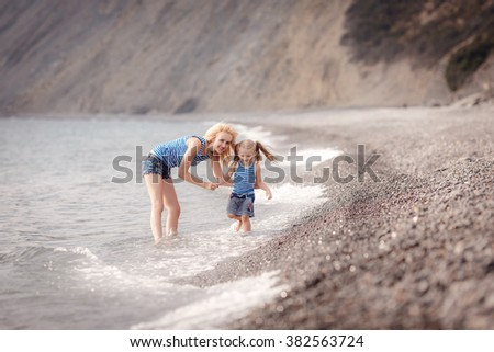 mother with child girl by the sea. Sunset portrait. Outdoor. Summer. Woman with girl. Happy family relaxing by sea - stock photo