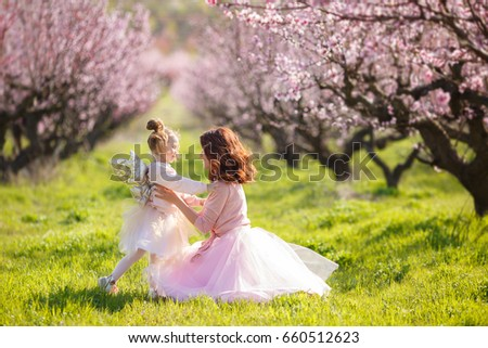 Mother with child girl playing in blooming spring garden. woman with daughter having fun outdoors in summer